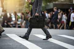 Businessman crossing the street on crosswalk and honding a laptop bag and smatphone Royalty Free Stock Images