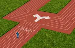 Businessman Crossroads. Concept choosing the right path as a man on a track and field sport track facing a difficult choice and dilemma with  two different Royalty Free Stock Photos