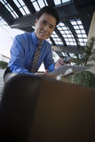 Businessman crouching, holding document and mobile phone, briefcase in foreground, smiling, portrait Stock Image