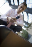 Businessman crouching, using mobile phone, focus on briefcase in foreground (tilt) Stock Image