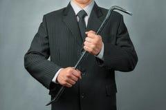 Businessman with crowbar Stock Photos