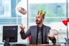 The businessman with crown and money sacks in the office Stock Images