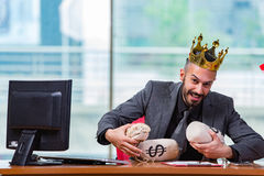 The businessman with crown and money sacks in the office Stock Photography
