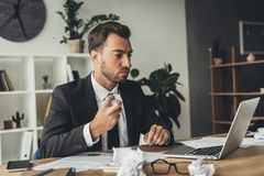 Young businessman with crumpled papers. On worktable stock images