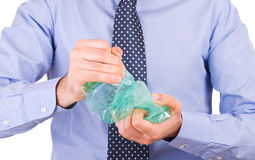 Businessman crushing a green bottle. Royalty Free Stock Photo