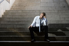 Businessman crying lost in depression sitting on street concrete stairs Royalty Free Stock Photos