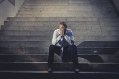 Businessman crying lost in depression sitting on street concrete stairs. Young business man drug addict or alcoholic crying abandoned lost in depression sitting Stock Photo