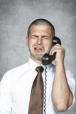 Businessman crying while talking on the phone Stock Photo