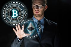 Businessman with cryptocurrency holograms Stock Photo