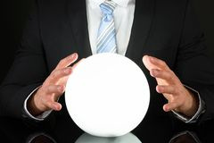 Businessman with crystal ball. Close-up Of Businessman Hand On Crystal Ball