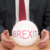 Businessman with crystal ball, square crop, differential focus. Brexit means an uncertain future UK at least in the short term Royalty Free Stock Image