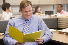 Businessman in cubicle with folder smiling Stock Image