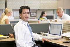 Businessman in cubicle with laptop. Looking at camera Stock Photos