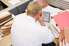 Businessman in cubicle with laptop Royalty Free Stock Photo