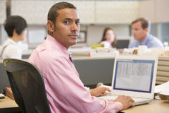 Businessman in cubicle with laptop. Businessman working in office cubicle smiling Stock Photo