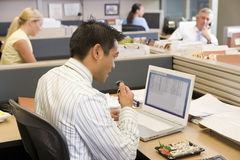 Businessman in cubicle at laptop eating sushi Stock Photography