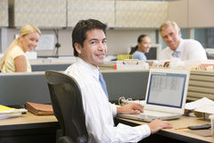 Businessman in cubicle with laptop smiling Royalty Free Stock Images