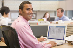 Businessman in cubicle with laptop smiling. Businessman working in office cubicle smiling Royalty Free Stock Photo