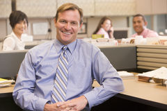 Businessman in cubicle smiling Royalty Free Stock Image