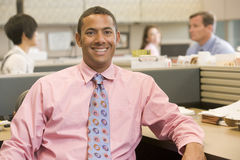 Businessman in cubicle smiling Stock Photography