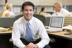 Businessman in cubicle smiling. At camera Royalty Free Stock Photos
