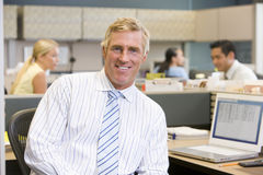 Businessman in cubicle smiling Stock Photos