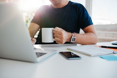 Businessman with cup of coffee working on laptop Royalty Free Stock Photo