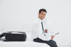 Businessman with cup and newspaper by luggage at a hotel room Stock Photo