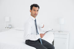 Businessman with cup reading newspaper at a hotel room Royalty Free Stock Photography