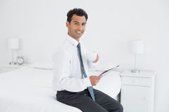 Businessman with cup reading newspaper at hotel room Royalty Free Stock Photo