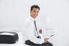 Businessman with cup reading newspaper at a hotel room Stock Photos