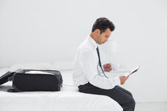Businessman with cup reading newspaper at hotel room Royalty Free Stock Photography