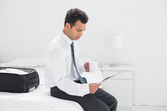 Businessman with cup reading newspaper at hotel room Royalty Free Stock Image
