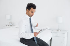 Businessman with cup reading newspaper at a hotel room Royalty Free Stock Image