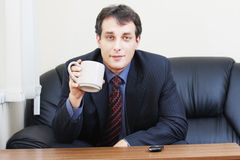Businessman with cup sitting on sofa Royalty Free Stock Image