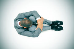 Businessman curled up in the floor with his head between his kne Royalty Free Stock Photos
