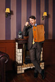 Businessman cursing on the phone, holding a suitcase. Royalty Free Stock Photos