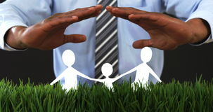 Businessman with cutout paper chain family with the protection of hands. On grass in office 4k stock footage