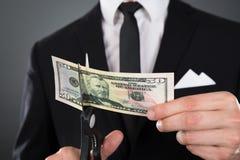 Businessman cutting dollar bill with scissors Stock Photo