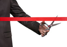 A businessman cutting a scarlet ribbon Royalty Free Stock Photos