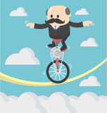 Businessman cycling balancing on a rope Royalty Free Stock Photography