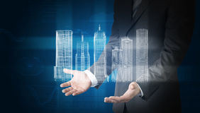 Businessman with 3d city model and graphs. Businessman with 3d model of city in hands on abstract blue background with graphs Stock Photography