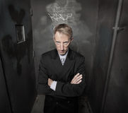 Businessman in a dark grungy background Royalty Free Stock Image
