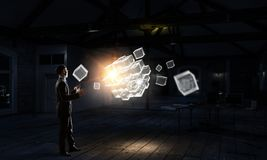 Innovative technologies integration. Mixed media. Businessman in dark office and cube figure. Mixed media Royalty Free Stock Photo