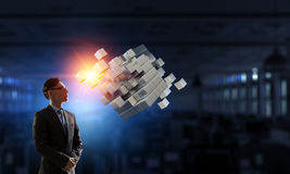 Innovative technologies integration. Mixed media. Businessman in dark office and cube figure. Mixed media Stock Image