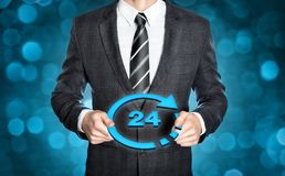 Businessman holding 24h sign. Businessman in a dark suit is holding a digital 24h sign in both hands Stock Images