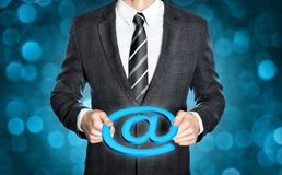 Businessman holding an @-sign. Businessman in a dark suit is holding a digital @-symbol in both hands Stock Photos