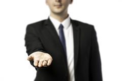 Businessman in dark suit holds out his hand flat Stock Image