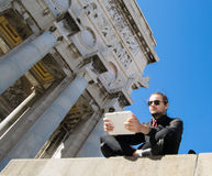 Businessman with dark suit and tablet - beautiful decorated architectonic background Royalty Free Stock Photography