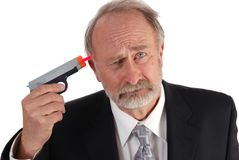 Businessman dart gun. Businessman with a dart gun to his head looking depressed. Poor business theme Royalty Free Stock Images